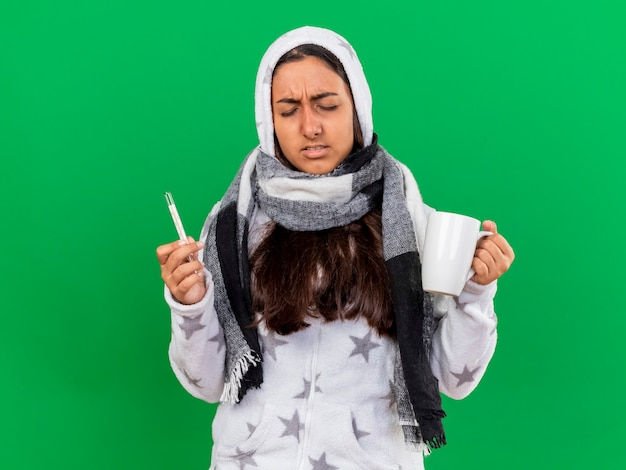Unpleased young ill girl with closed eyes putting on hood wearin scarf holding thermometer with cup of tea isolated on green background