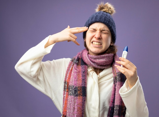 紫色で隔離されたピストルジェスチャーで自殺を示す温度計を保持しているスカーフと白いローブと冬の帽子を身に着けている目を閉じて不機嫌な若い病気の女の子