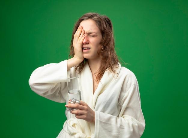 緑で隔離の顔に手を置いて水のガラスを保持している白いローブを着て目を閉じて不機嫌な若い病気の女の子