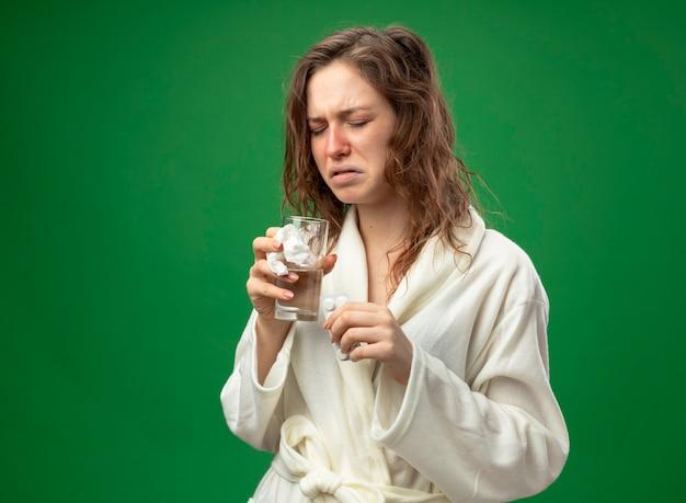 緑で隔離の丸薬と水のガラスを保持している白いローブを着て目を閉じて不機嫌な若い病気の女の子