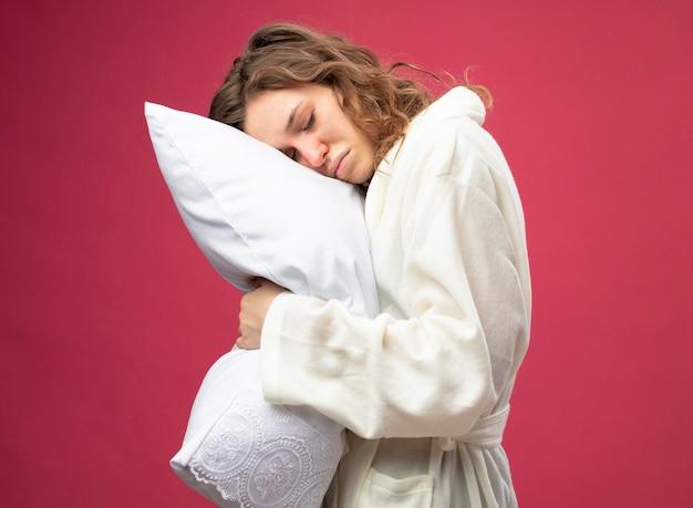 Недовольная молодая больная девушка с закрытыми глазами в белом халате обняла подушку, изолированную на розовом