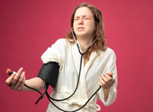 분홍색에 고립 된 혈압계로 자신의 압력을 측정하는 흰 가운을 입고 닫힌 눈을 가진 불쾌한 어린 아픈 소녀