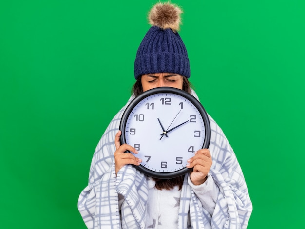 Unpleased young ill girl with closed eyes wearing winter hat with scarf covered face with wall clock isolated on green background