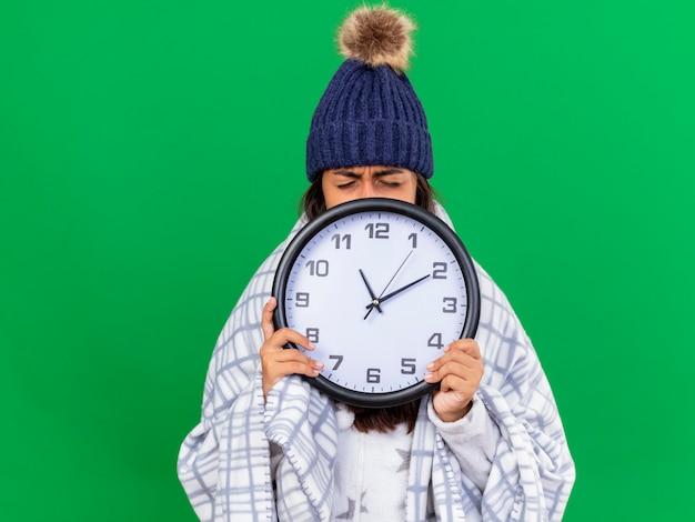 Soddisfatta giovane ragazza malata con gli occhi chiusi che indossa cappello invernale con sciarpa viso coperto con orologio da parete isolato su sfondo verde