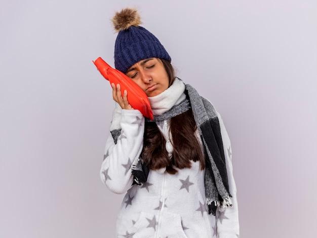 Giovane ragazza malata dispiaciuta con gli occhi chiusi che indossa cappello invernale con sciarpa che mette la borsa dell'acqua calda sulla guancia