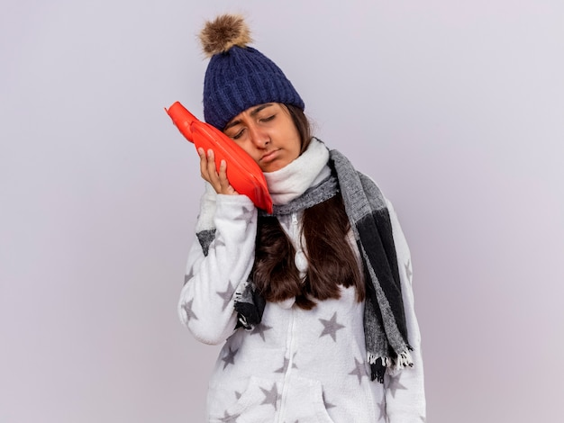 뺨에 뜨거운 물 주머니를 두는 스카프로 겨울 모자를 쓰고 닫힌 눈을 가진 불쾌한 어린 아픈 소녀