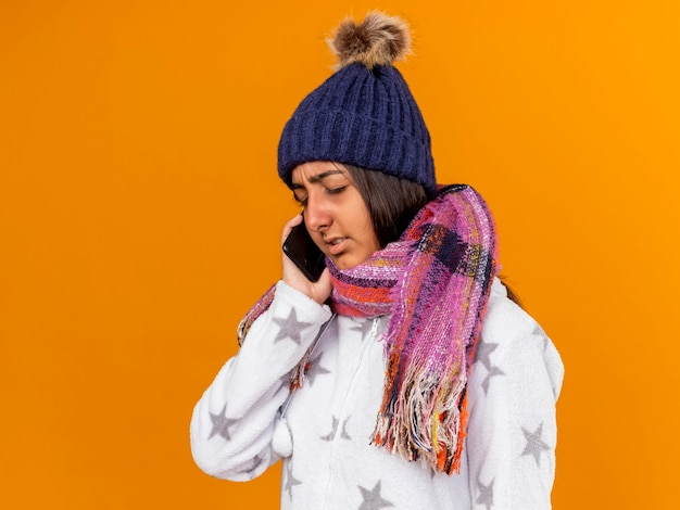 Giovane ragazza malata dispiaciuta con gli occhi chiusi che indossa il cappello invernale con sciarpa parla al telefono isolato su sfondo giallo