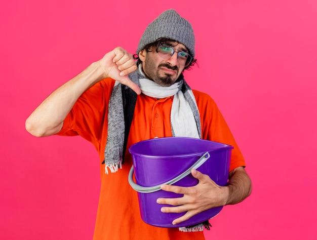 Giovane uomo malato dispiaciuto che indossa occhiali inverno cappello e sciarpa tenendo il secchio di plastica guardando la parte anteriore che mostra il pollice verso il basso isolato sulla parete rosa con spazio di copia