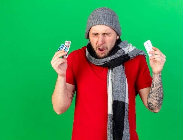 겨울 모자와 스카프를 착용하는 불쾌한 젊은 아픈 남자는 녹색 벽에 고립 된 의료 약 팩을 보유하고 있습니다.