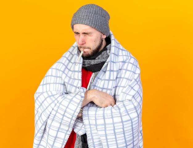 격자 무늬에 싸여 겨울 모자와 스카프를 착용하는 불쾌한 젊은 아픈 남자는 주황색 벽에 고립 된 입에 온도계를 유지하는 교차 팔로 서 있습니다.
