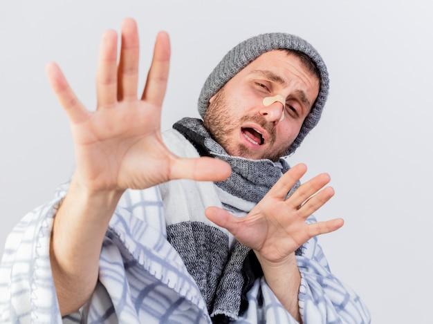 Giovane uomo malato dispiaciuto che indossa cappello invernale e sciarpa avvolto in un plaid con intonaco sul naso tendendo le mani alla telecamera isolata su bianco