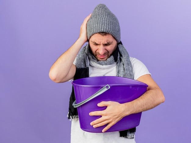 紫色の背景で隔離の頭に手を置くプラスチック製のbusketを保持している吐き気を持っているスカーフと冬の帽子をかぶって不機嫌な若い病気の男