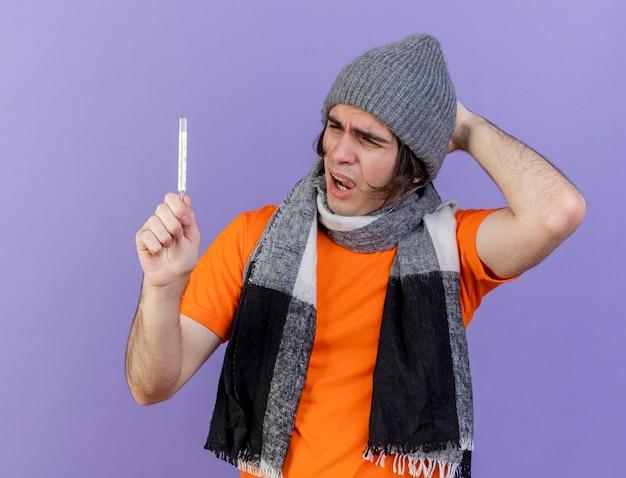 紫色の背景で隔離の頭に手を置いてスカーフを保持し、温度計を見て冬の帽子をかぶって不機嫌な若い病気の男