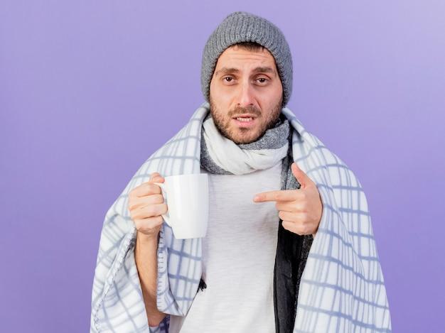 スカーフを保持し、紫色の背景で隔離のお茶のカップを指す冬の帽子をかぶって不機嫌な若い病気の男