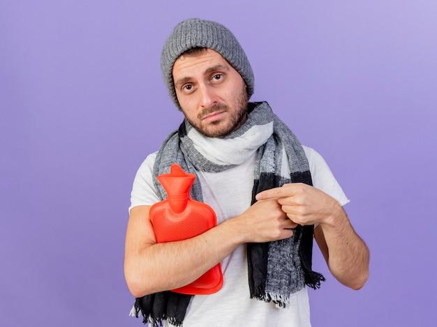 スカーフを保持し、紫に分離された湯たんぽを指差して冬の帽子をかぶって不機嫌な若い病気の男
