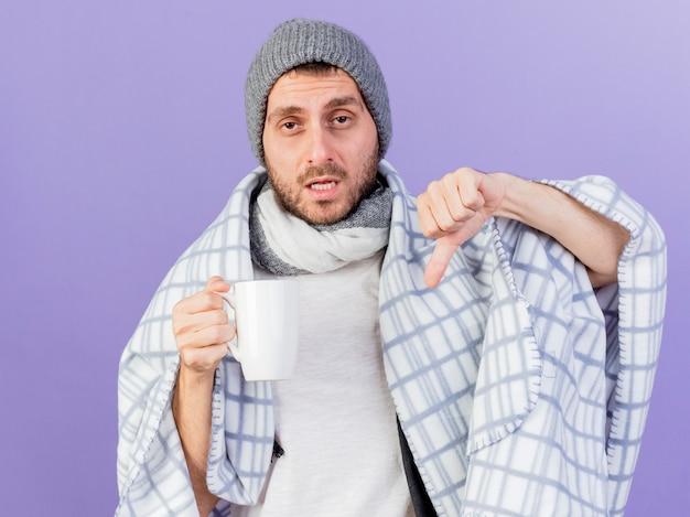 紫色の背景で隔離の親指を下に示すお茶のカップを保持しているスカーフと冬の帽子をかぶって不機嫌な若い病気の男