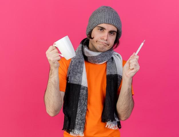 Giovane uomo malato dispiaciuto che indossa cappello invernale con sciarpa che tiene tazza di tè con termometro isolato sul colore rosa