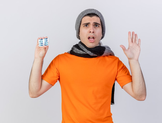 錠剤を保持し、白で隔離の停止ジェスチャーを示すスカーフと冬の帽子をかぶって不機嫌な若い病気の男