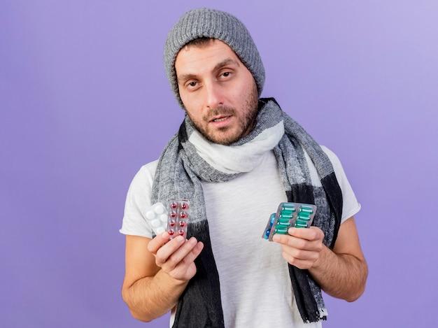 紫色の背景で隔離の丸薬を保持しているスカーフと冬の帽子をかぶって不機嫌な若い病気の男