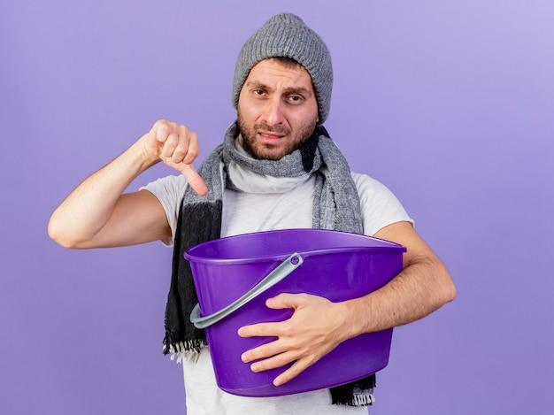 Giovane uomo malato dispiaciuto che indossa il cappello invernale con sciarpa che tiene il cestino di plastica che mostra il pollice verso il basso isolato su sfondo viola
