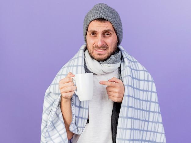 Il giovane uomo malato dispiaciuto che porta il cappello di inverno con la tenuta della sciarpa e punti alla tazza di tè isolata su fondo viola
