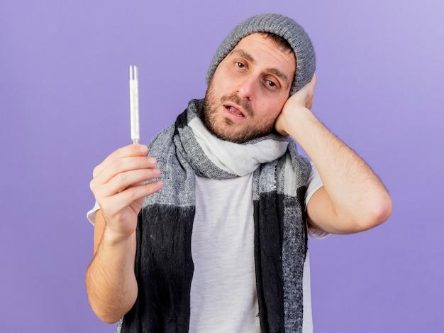 温度計を保持し、紫色の背景で隔離の頭に手を置くスカーフと冬の帽子をかぶって不機嫌な若い病気の男