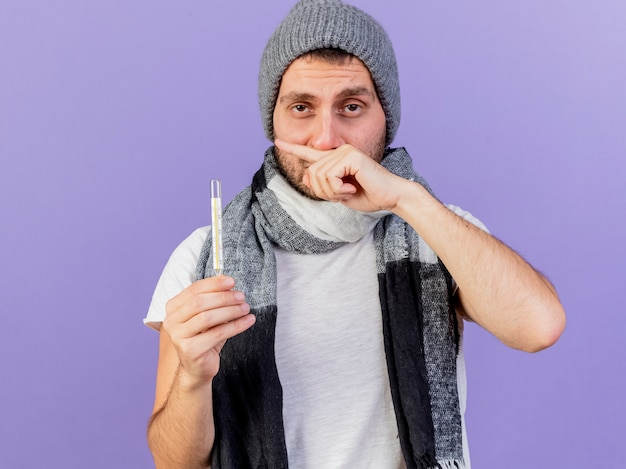 紫色の背景で隔離の手で温度計ワイピング鼻を保持しているスカーフと冬の帽子をかぶって不機嫌な若い病気の男