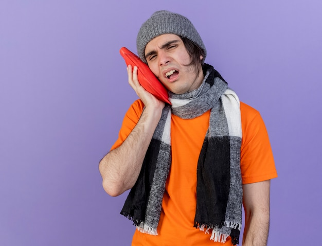Unpleased young ill man wearing winter hat with scarf putting hot water bag on cheek isolated on purple