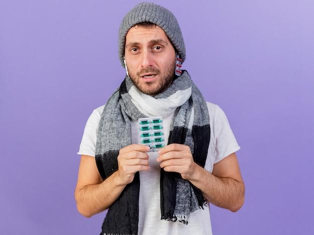 帽子の下に丸薬を置き、紫色の背景で隔離の丸薬を保持しているスカーフと冬の帽子をかぶって不機嫌な若い病気の男