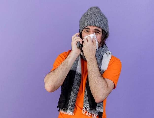Il giovane malato dispiaciuto che indossa il cappello invernale con sciarpa parla al telefono e asciugandosi il naso con un tovagliolo isolato su sfondo viola