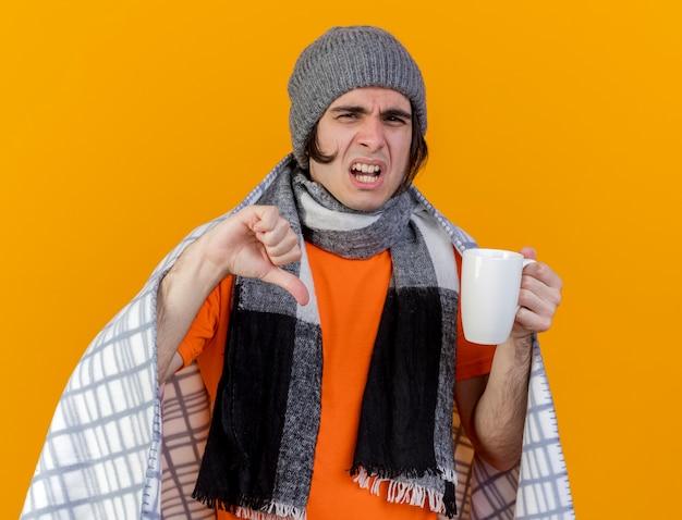 Giovane uomo malato dispiaciuto che indossa il cappello invernale con sciarpa avvolta in una tazza di tè che tiene il plaid che mostra il pollice verso il basso isolato su sfondo arancione