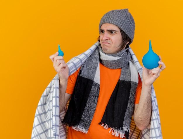 Giovane uomo malato dispiaciuto che indossa cappello invernale con sciarpa avvolta in plaid holding e guardando clistere isolato su sfondo arancione