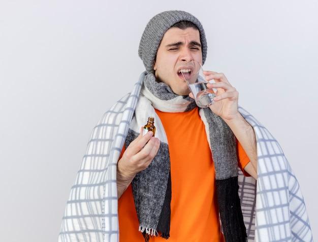 Giovane uomo malato dispiaciuto che indossa il cappello invernale con sciarpa avvolta in un plaid che tiene la medicina in una bottiglia di vetro e acqua potabile isolato su sfondo bianco