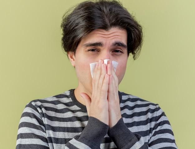 Недовольный молодой больной вытирает нос салфеткой на оливково-зеленом фоне