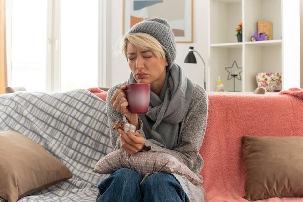 거실에서 소파에 앉아 컵과 약 물집 팩을 들고 겨울 모자를 쓰고 그녀의 목에 스카프를 가진 불쾌한 젊은 아픈 슬라브 여자