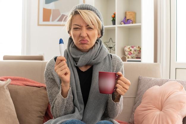 거실에서 소파에 앉아 온도계와 컵을 들고 겨울 모자를 쓰고 그녀의 목에 스카프를 가진 불쾌한 젊은 아픈 슬라브 여자