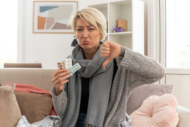 Scontento giovane malata donna slava con sciarpa intorno al collo avvolto in plaid tenendo medicine blister e pollice verso il basso seduto sul divano in soggiorno