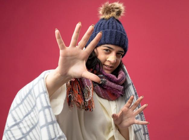 Giovane donna malata dispiaciuta che indossa un cappello invernale e una sciarpa avvolti in un plaid guardando la parte anteriore che allunga le mani con intonaco sul naso isolato sul muro rosa