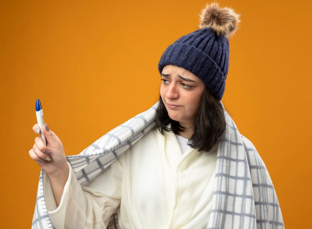 オレンジ色の壁に隔離された格子縞の保持と正面を見て包まれたローブの冬の帽子を身に着けている不機嫌な若い病気の女性