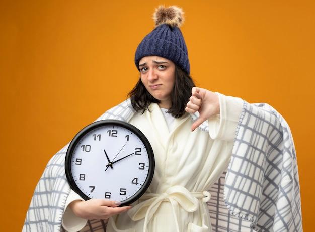Giovane donna malata dispiaciuta che indossa il cappello invernale della veste avvolto in un plaid che tiene l'orologio che guarda davanti che mostra il pollice verso il basso isolato sulla parete arancione