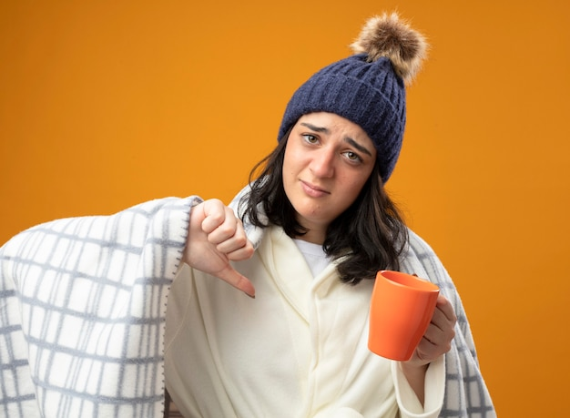 Giovane donna malata dispiaciuta che indossa il cappello invernale della veste avvolto in un plaid che tiene una tazza di tè guardando la parte anteriore che mostra il pollice verso il basso isolato sulla parete arancione