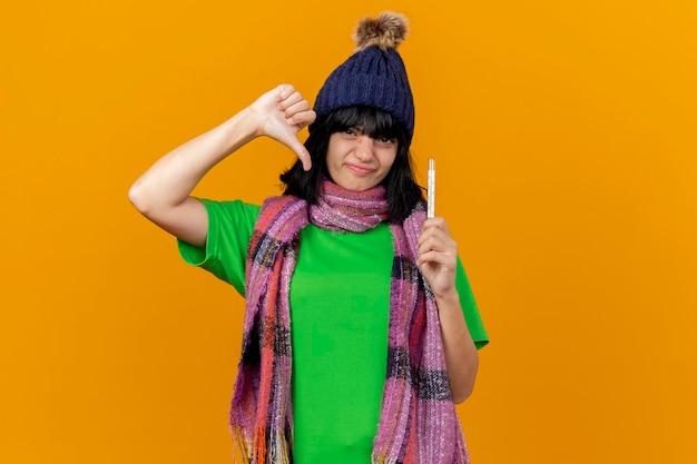 Giovane donna malata dispiaciuta che indossa cappello invernale e sciarpa che tiene il termometro guardando la parte anteriore che mostra il pollice verso il basso isolato sulla parete arancione con lo spazio della copia