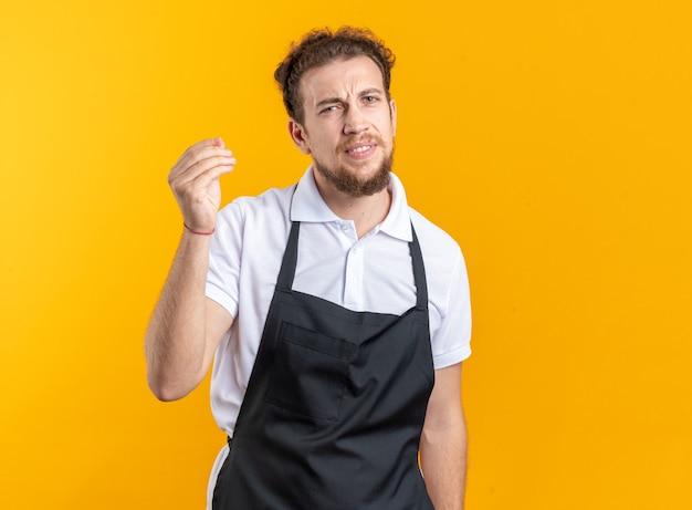 黄色の背景で隔離の先端ジェスチャーを示す制服を着て不機嫌な若い男性理髪師
