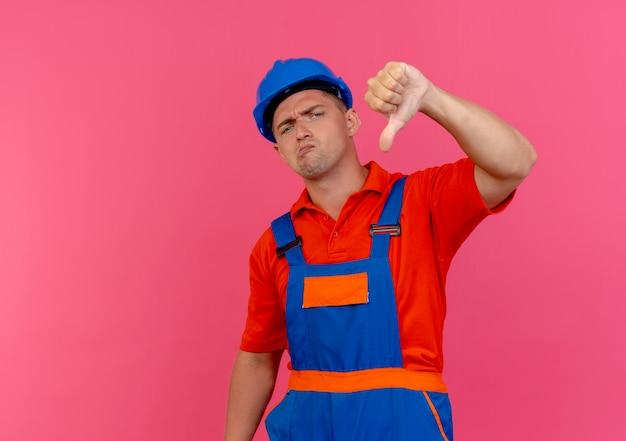 Недовольный молодой мужчина-строитель в униформе и защитном шлеме с большим пальцем на розовом