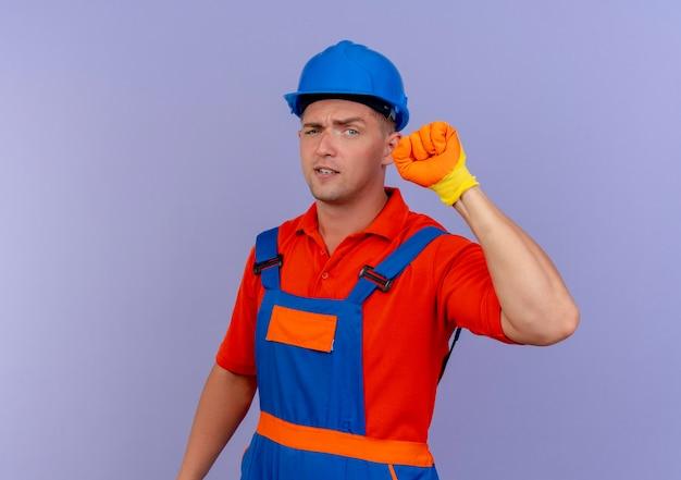紫色の拳を上げる手袋で制服と安全ヘルメットを身に着けている不機嫌な若い男性ビルダー