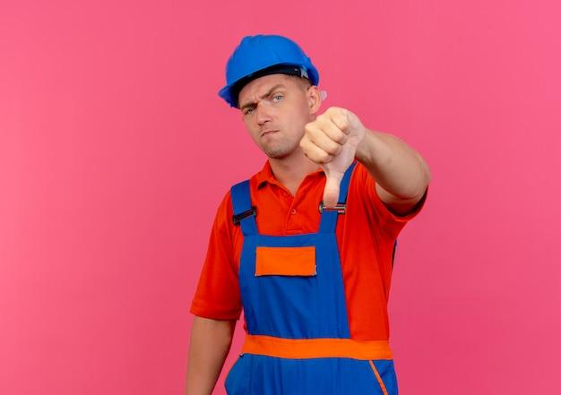 Giovane costruttore maschio dispiaciuto che indossa l'uniforme e il casco di sicurezza con il pollice in giù sul rosa
