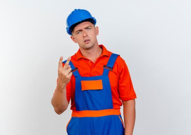 Giovane costruttore maschio dispiaciuto che indossa l'uniforme e il casco di sicurezza che mostra due su bianco
