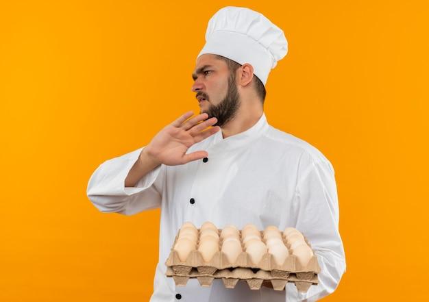 Giovane cuoco maschio dispiaciuto in cartone uniforme della tenuta del cuoco unico delle uova che esaminano il lato e che gesturing nessun isolato sullo spazio arancio