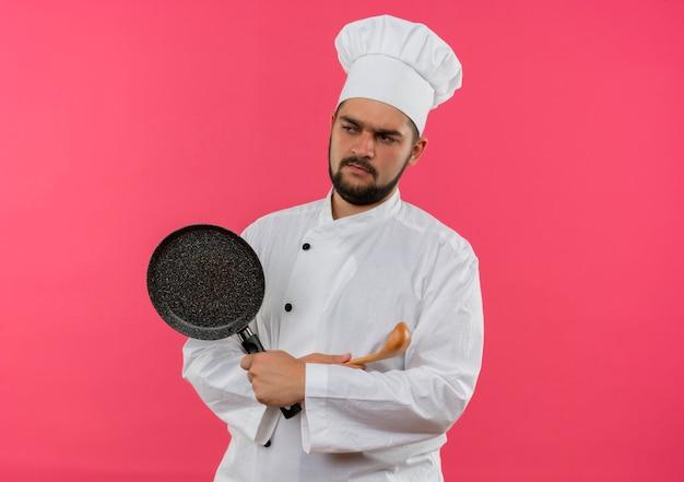 Insoddisfatto giovane cuoco maschio in uniforme da chef in piedi con postura chiusa e tenendo la padella con cucchiaio guardando lato isolato su spazio rosa