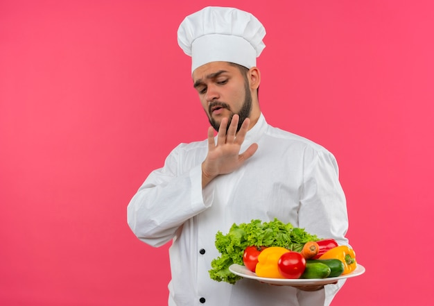 野菜のプレートを持って見て、ピンクの空間に孤立していないジェスチャーをしているシェフの制服を着た不機嫌な若い男性料理人